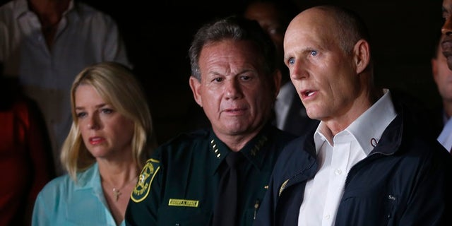 A state representative called on Gov. Rick Scott (right) to remove Sheriff Scott Israel (middle) from his position.