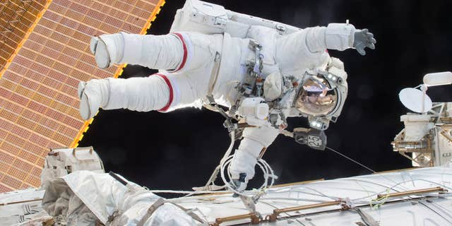 Expedition 46 Commander Scott Kelly on a Dec. 21, 2015 spacewalk, in which Kelly and Flight Engineer Tim Kopra successfully moved the International Space Station's mobile transporter rail car ahead of Wednesday's docking of a Russian cargo supply spacecraft.