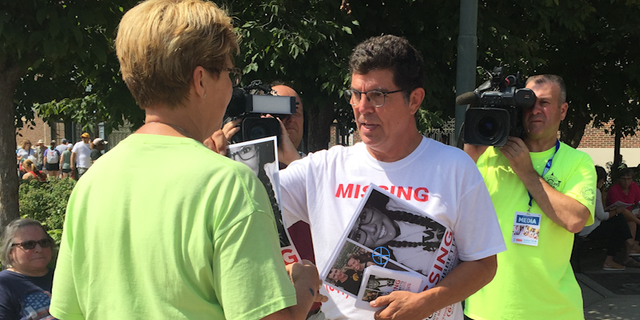 Rob Tibbetts, Mollie's father, hands out posters in search for his missing daughter.