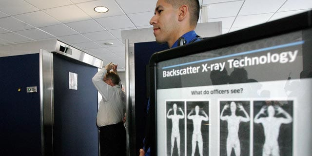 File: Transportation Security Administration employee Anthony Brock, left, demonstrates a new full-body scanner at San Diego's Lindbergh Field.
