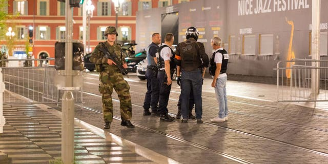 Police officers and a soldier stand by the sealed off area of an attack in Nice, France in wake of a deadly terrorist attack that killed 84 people including 2 American tourists.