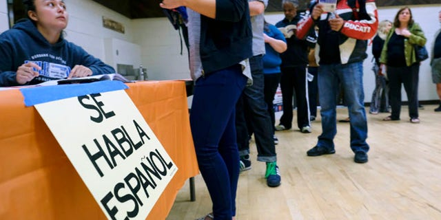 "A sign that reads ""Spanish is Spoken Here"" hangs as voters check in at the North Hollywood Amelia Earhart Regional Library polling station in Los Angeles on Tuesday, Nov. 8, 2016. (AP Photo/Richard Vogel)"