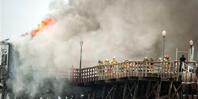 Firefighters contend with a fire burning on the Seal Beach pier in Seal Beach, Calif. on Friday, May 20, 2016. (Ken Steinhardt/The Orange County Register via AP)