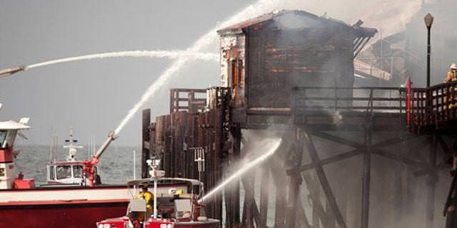 Fireboats from Long Beach hit the fire inside the closed Ruby's Diner at the end of the Seal Beach pier in Seal Beach, Calif. on Friday, May 20, 2016. (Ken Steinhardt/The Orange County Register via AP)