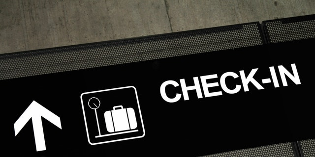 Airport sign pointing to check-in area, placed on exposed concrete beam.