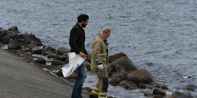 Police officers search off the south coast of the isle of Amager, near Copenhagen, Denmark.