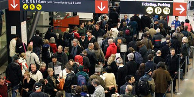 In this file photo taken Dec. 27, 2010, travelers wait in a TSA security checkpoint line at Seattle-Tacoma International Airport.