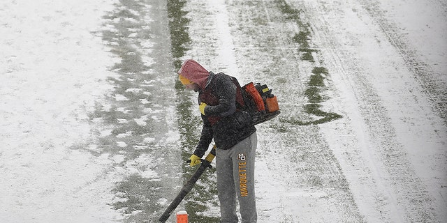 Workers clears snow from Soldier Field before an NFL football game between the Chicago Bears and Cleveland Browns in Chicago, Sunday, Dec. 24, 2017.