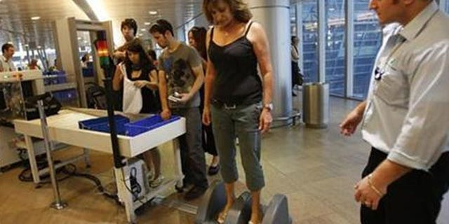 An Israeli woman stands on a step-on scanner during a security check at Ben Gurion airport near Tel Aviv.