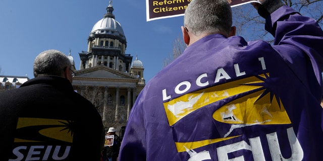 In this March 20, 2014 file photo, members of the Service Employees International Union, SEIU, rally in front of the Illinois State Capitol in support of Immigration changes.