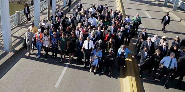 March 7, 2015: President Obama, first lady Michelle Obama, Malia and Sasha as well as members of Congress, former President George W. Bush and his wife Laura, and civil rights leaders make a symbolic walk across the Edmund Pettus Bridge in Selma, Ala.