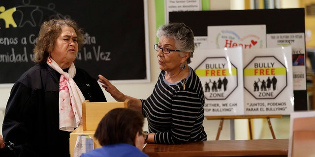 Two women talk in front of anti-bullying signs at the 30th Street Senior Center in San Francisco, April 13, 2018.