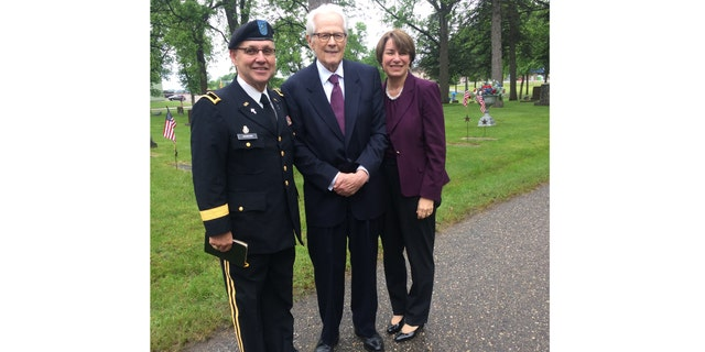 Klobuchar, right, is pictured with retired Brigadier General Dean Johnson, left, and Don Franklin, center, at Saturday's burial ceremony in Willmar, Minn.