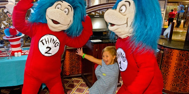 """A girl enjoys some time with Thing  1 and 2 during """"The Green Eggs and Ham Breakfast with the Cat in the Hat and Friends"""" onboard the Carnival Freedom. The featured dining opportunity with characters out of Dr. Seuss' books is staged in the Carnival Freedom's Chic Dining Room and offers playful foods straight from Dr. Seuss's imagination – green eggs and ham, moose juice and goose juice, along with colorful fruit and pancake stacks, funky French toast and more. (Andy Newman/Carnival Cruise Lines)"""
