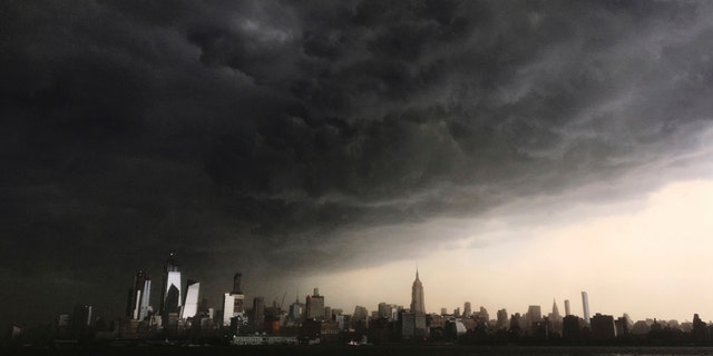 In this Tuesday, May 15, 2018 photo, storm clouds gather over New York city seen from the Hudson River. A line of strong storms pushed across New York City and generated a small tsunami off the coast.
