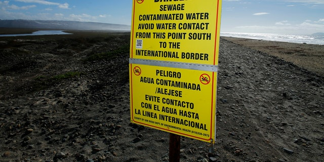 Contaminated water signs are placed along the sand following a rain storm in Imperial Beach, California December 4, 2014. The alert was issued because of a rain-driven influx of sewage-fouled water from the Tijuana River, according to the San Diego County Department of Environmental Health.