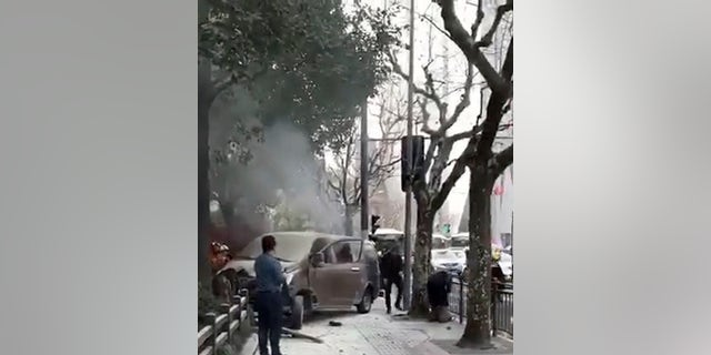 Rescuers attended to victims after a minivan carrying gas tanks plowed into pedestrians along a street in Shanghai, Friday, Feb. 2, 2018.
