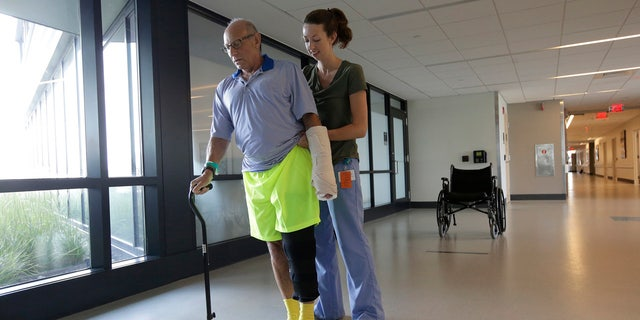 William Lytton, of Scarsdale, N.Y., left, is assisted by physical therapist Caitlin Geary at Spaulding Rehabilitation Hospital, in Boston, Tuesday, Aug. 28, 2018, while recovering from a shark attack.