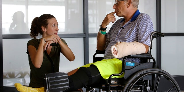 William Lytton, of Scarsdale, N.Y., right, speaks with physical therapist Caitlin Geary during physical therapy at Spaulding Rehabilitation Hospital, in Boston, Tuesday, Aug. 28, 2018, while recovering from a shark attack.