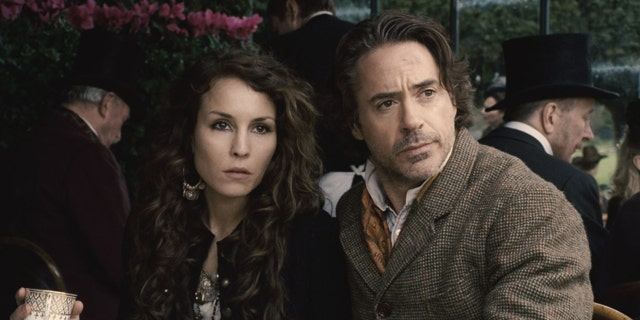 """In this film image released by Warner Bros. Pictures, Noomi Rapace, left, and Robert Downey Jr. are shown in a scene from """"Sherlock Holmes: A Game of Shadows."""""""