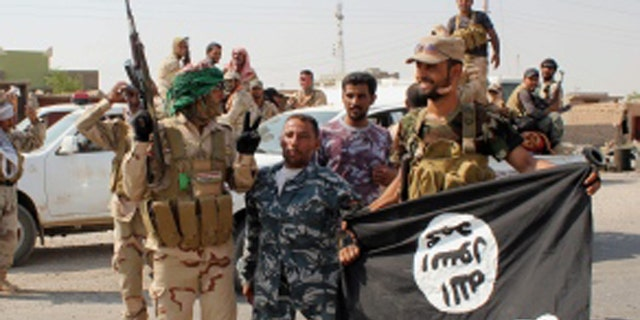 Shia militias, shown here in 2014 holding a captured ISIS flag from an operation near Baghdad, have been accused by Amnesty International of operating outside the law.