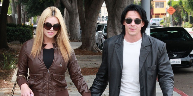 """Francis """"Coyote"""" Shivers walks out of Hollywood police station with his wife."""