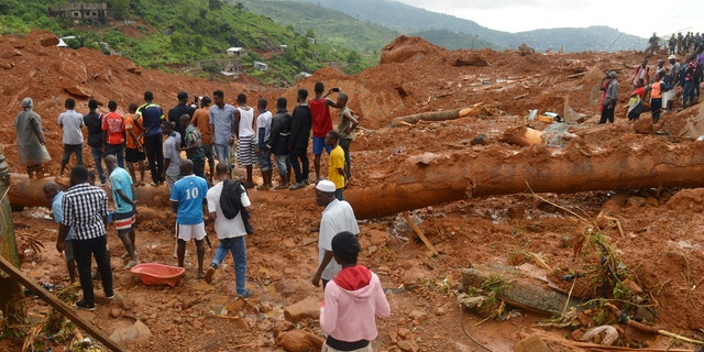 Residents stand as rescue workers search for survivors after a mudslide in the mountain town of Regent, Sierra Leone August 14, 2017.