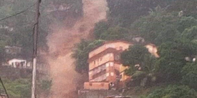 In this image made available by Society 4 Climate Change Communication, Sierra Leone, mud and water cascades down the side on a hill in Freetown, Sierra Leone Monday Aug. 14, 2017.