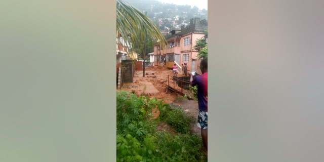 In this image made available by Society 4 Climate Change Communication, Sierra Leone, mud and water cascades near houses in Freetown, Sierra Leone Monday Aug. 14, 2017.