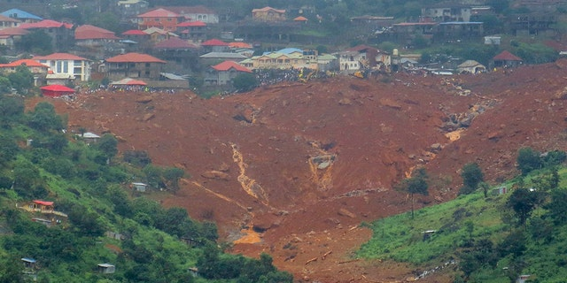 Rescue workers gather at the summit of a mudslide in Regent, east of Freetown, Sierra Leone, Monday, Aug. 14 , 2017.