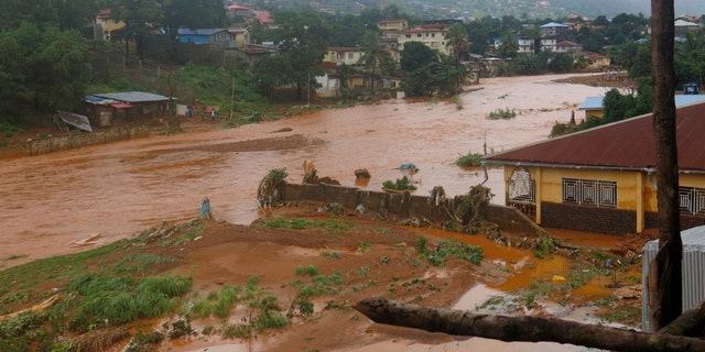 A torrent of water flows through a flooded neighbourhood in Regent, east of Freetown, Sierra Leone Monday, Aug. 14 , 2017.