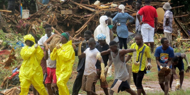 Rescue workers carry the body of a victim from the site of a mudslide in Regent, east of Freetown, Sierra Leone, Monday, Aug. 14, 2017.