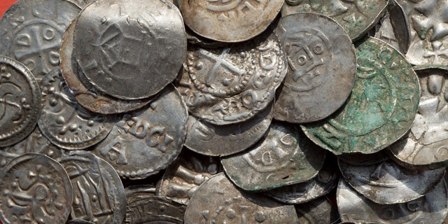 This April 13, 2018 photo shows medieval Saxonian, Ottoman, Danish and Byzantine coins found near Schaprode on the northern German island of Ruegen in the Baltic Sea. (Stefan Sauer/dpa via AP)