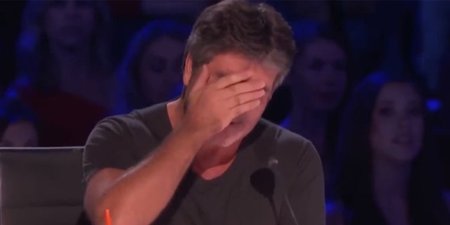 "Simon Cowell attempts to hide his tears after an emotional performance from a contestant on ""America's Got Talent."""