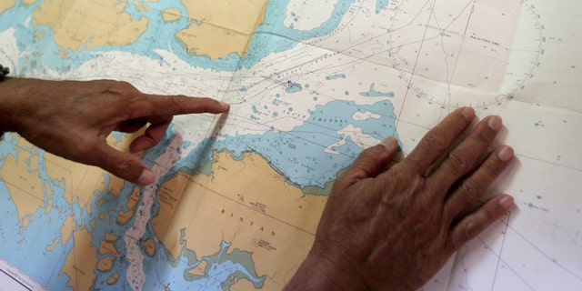 Tan Hua Chiow, a retired Singapore naval officer, shows a naval chart and explains to the Associated Press the flow of traffic at sea.