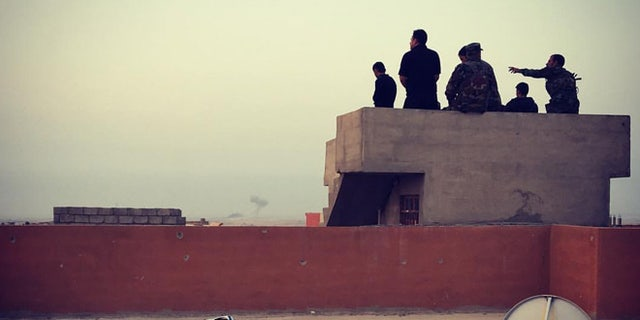 Men guard the city from rooftops, as ISIS remains just miles away after being pushed out of Sinjar a year ago.