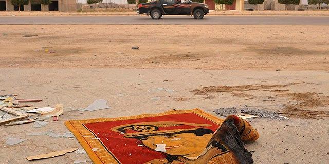 Oct. 3: A carpet depicting Muammar Qaddafi is seen on the road after Libyan revolutionary fighters took the village of Abu Hadi, near Sirte, Libya.