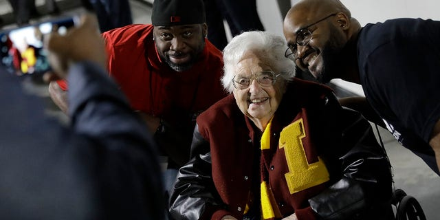 Sister Jean Dolores Schmidt, 98, the team chaplain for Loyola-Chicago, poses for a photo with fans at an NCAA men's basketball tournament game in Atlanta, March 24, 2018.