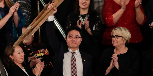 Ji Seong-ho holds up his crutches after his introduction by President Trump during the State of the Union address to a joint session of Congress on Capitol Hill