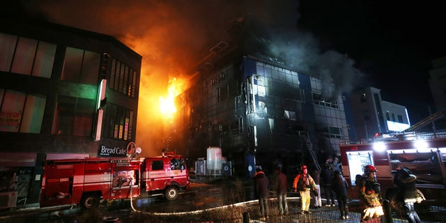 Firefighters try to extinguish a fire at an eight-floor building in Jecheon, South Korea, Thursday, Dec. 21, 2017. (Kim Hyung-woo/Yonhap via AP)