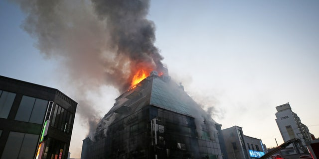 Smoke rises as firefighters try to extinguish a fire at an eight-floor building in Jecheon, South Korea, Thursday, Dec. 21, 2017.