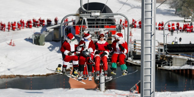 Skiers dressed as Santa Claus ride the chairlift at a resort in Newry, Maine.