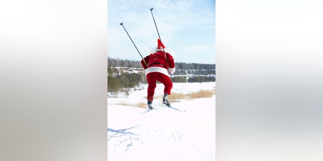 Rear view of Santa Claus jumping on skies