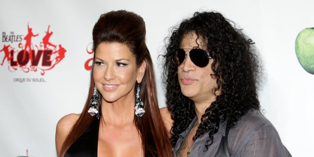 "Perla Hudson (L) and Slash arrive for the fifth anniversary celebration of ""The Beatles LOVE by Cirque du Soleil"" show at the Mirage Hotel and Casino in Las Vegas, Nevada June 8, 2011. REUTERS/Steve Marcus (UNITED STATES - Tags: ENTERTAINMENT) - RTR2NGWG"