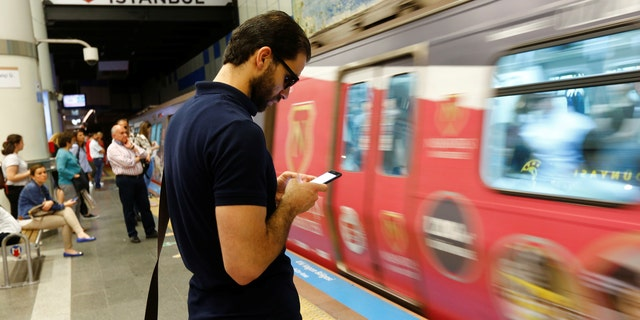 File photo: A passenger uses his smartphone as he waits for the train at a subway station in Istanbul, Turkey, June 14, 2017. (REUTERS/Murad Sezer)