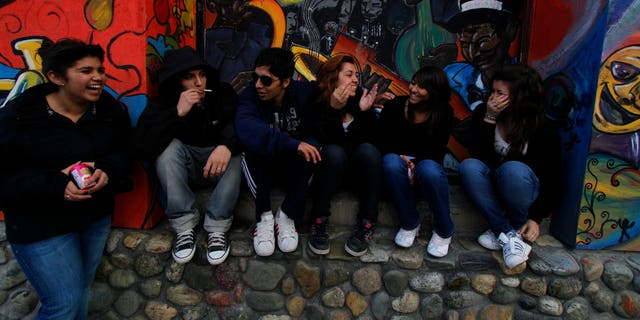 Teenagers smoke and talk in front of a vacant business in Ushuaia, Argentina.  REUTERS/Jim Urquhart