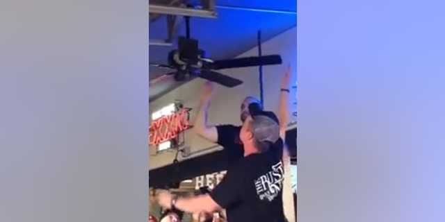 The snake wrapped itself around the bar's ceiling fan on Saturday. Staff later removed and released it.