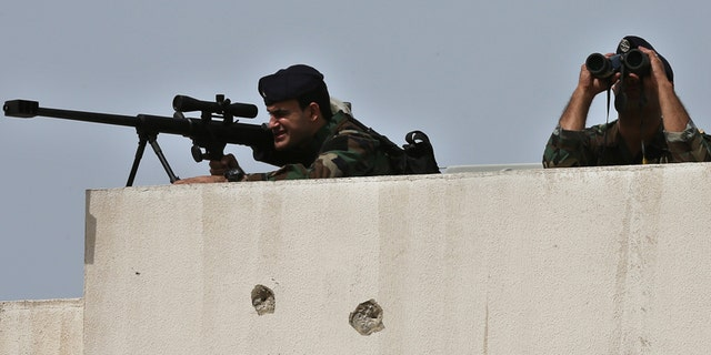 Lebanese army snipers take their positions on the top of a building, in Tripoli in  2016.