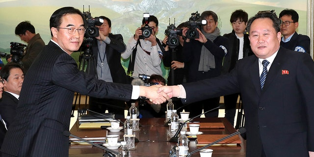 South Korean Unification Minister Cho Myoung-gyon, left, shakes hands with the head of North Korean delegation Ri Son Gwon before their meeting at the Panmunjom in the Demilitarized Zone in Paju, South Korea, Tuesday, Jan. 9, 2018.