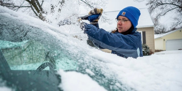 Colleen Streefland brushes snow and ice off her vehicle in Rochester, Minn., April 14, 2018.